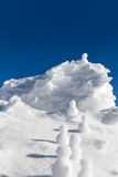 Snowmen climbing up to a icy mountaintop Stock Photography