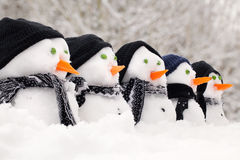 Snowmen close up in a row. With hats and scarfs Royalty Free Stock Images