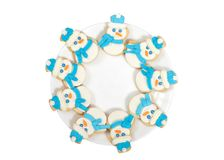 Snowmen cookies on a plate flat view isolated on white. Snowman sugar cookies decorated with marshmallow fondant, blue royal icing scarf and hats arranged in a Stock Image