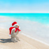 Snowmen couple at sea beach in christmas hat. Smiley sandy snowmen couple at sea beach in christmas hat. New years holiday in hot countries concept Stock Photo