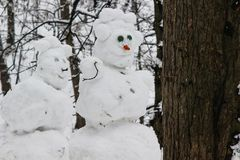Snowmen couple in the winter forest. Made by hand. Close up royalty free stock photo