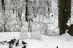 Snowmen couple in the winter forest. Pigeons peck bread pieces. Made by hand royalty free stock image