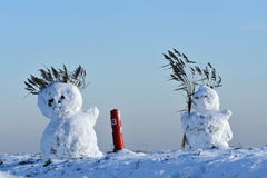 Snowmen on dike Stock Photo