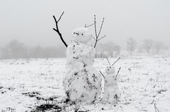 Snowmen from dirty snow on the background of trees and fog royalty free stock photography