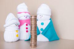 Snowmen family look at big stack of coins Stock Photos