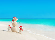 Snowmen family at tropical beach in santa hats. New Years and Ch