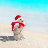 Snowmen friends at sea beach in christmas hat. Royalty Free Stock Photo