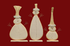 Snowmen on a red background. A trip of winter snowmen on a red background Royalty Free Stock Photo