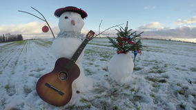 Snowmen with retro guitar and christmas fir tree on field, time lapse 4K. Funny happy new year snowmen with retro guitar and christmas fir tree on field, time stock video footage