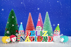 Snowmen and sheep Christmas Greeting in Spanish. Feliz Navidad, Merry Christmas in Spanish colorful wood sign, red, pink, green pine trees with snowman and stock photo