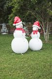 Snowmen. Spherical snowmen in a park with a pine trees and a house as background Royalty Free Stock Photo
