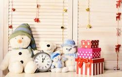 Snowmen, teddy bears and present boxes near alarm clock royalty free stock photos