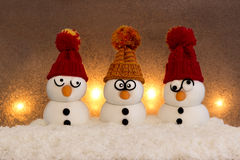 Snowmen. Three snowmen sitting in the snow in front of a  background lightened with candles Royalty Free Stock Image