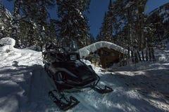 Snowmobile от шале дома в лесе зимы с снегом в ligh Стоковое Изображение