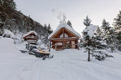 Snowmobile от шале дома в лесе зимы с снегом в moun Стоковое Изображение