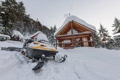 Snowmobile от шале дома в лесе зимы с снегом в moun Стоковая Фотография