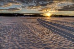Snowmobile следы возглавляя в заход солнца Стоковое Изображение