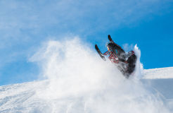 Snowmobile action. Snowmobile jump in deep snow and clear skies Stock Image