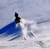 Snowmobile adventure. Man alone in the wilderness on snowmobile. Untouched nature and clean snow royalty free stock photography