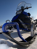 Snowmobile against a blue sky. Snowmobile against a blue sky from low point Royalty Free Stock Photo