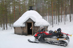 Snowmobile in front of Finnish Kota in a snow-covered landscape. Stock Photos