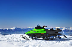 Snowmobile on mountain peak. Snowmobile against a deep blue sky in Sureanu mountains Romania Stock Photo