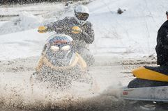 Snowmobile moves on bend of sport track Stock Photos