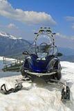 Snowmobile parkte im Berg auf schneebedeckten Steigungen Stockfotografie
