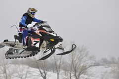 Snowmobile racer flying down the mountain Stock Photo