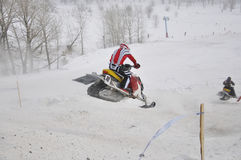 Snowmobile racer flying down the mountain Stock Images