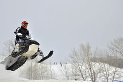 On the snowmobile rider flies sideways. On the snowmobile rider flies out the hillock of snow sideways royalty free stock photo