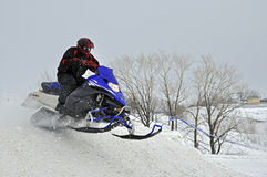 On the snowmobile rider jumps down the mountain. Snowmobile races, on the snowmobile rider jumps down the mountain royalty free stock image