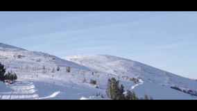 Snowmobile rides through the snowy mountains to the top stock video footage