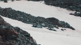 Snowmobile riding on snowy mountain hillside with climbers tourists. Snowmobile riding on snowy mountain rocky hillside with climbers tourists far away, sunny stock video