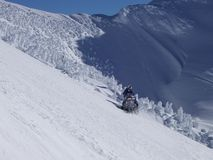 Snowmobile Run. Snowmobile on snow covered mountain stock image