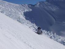 Snowmobile Run. Snowmobile on snow covered mountain Stock Image