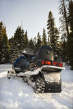 Snowmobile in snow. Snowmobile in snow with trees in background Royalty Free Stock Photo