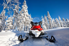 Snowmobile in snowy Finland. Red snowmobile in Finnish Lapland sunny landscape Stock Photos