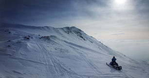 Snowmobile in snowy scenery  in blue. Snowmobile in snowy scenery in blue Royalty Free Stock Photo