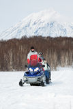 Snowmobile with tourists in sleigh rides on background of forest and volcano Royalty Free Stock Image