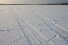 Snowmobile traces on the lake Stock Photos