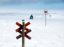 Snowmobile on track in winter scene. A snowmobile behind a red wooden signpost on a winter day in northern Sweden Royalty Free Stock Photography