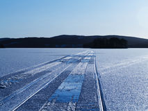 Snowmobile tracks on lake. Snowmobile tracks extending into the distance on a frozen lake, with trees and hills on the horizon Royalty Free Stock Images