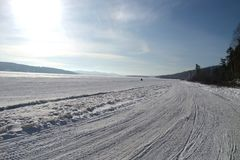 A snowmobile trail in winter in Quebec. A large snowmobile trail on a big lake in winter, in Quebec, Canada. A very cold day stock photography