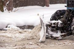 Snowmobile wiadro usuwa mokrego śnieg od drogi obraz stock