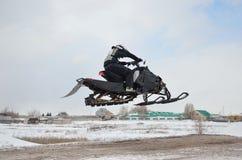 Snowmobilemitfahrer, der hohe Luft fliegt Stockbilder
