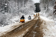 Snowmobilers. Three snowmobilers racing along rural Michigan road, with snow-frosted tree along the sides Stock Photo