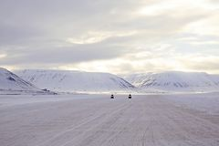 Snowmobiles Approaching, on Svalbard. Two Snowmobiles Approaching, Snowy Mountains in the Background. Svalbard, Norway royalty free stock photography