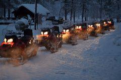 Snowmobiles heating up for an excursion Royalty Free Stock Photos