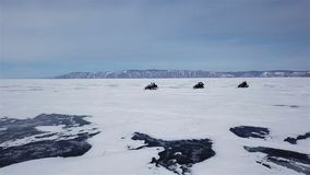 Aerial view snowmobiles ride on the frozen Lake Baikal in winter stock video footage